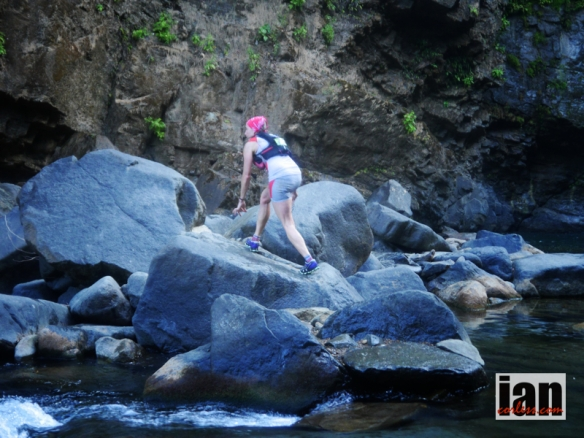Julia Bottger crossing the rocks at the waterfall section TCC2014 ©iancorless.com